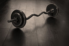 Heavy weight for fitness. Rod on the wooden floor Royalty Free Stock Photography
