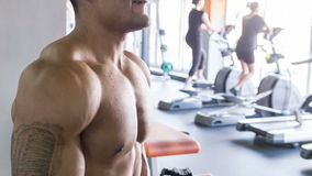 Heavy weight sportsman is training with dumbbells. Handsome sportsman is holding two dumbbells in both his hands at arm's length. At the end of the exercise he stock footage