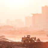 Heavy wheel excavator machine working at sunset Royalty Free Stock Image