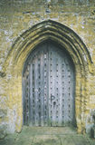 Heavy wooden door under archway at an English church Royalty Free Stock Image