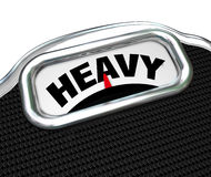 Heavy Word on Scale Measuring Weight or Mass Royalty Free Stock Images