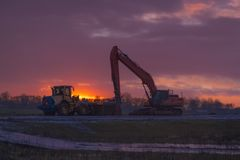 Heavy work machines at sunset. Including a bulldozer and crane stock image