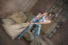 Heavy work. Young woman in dilapidated warehouse lifts heavy sack Royalty Free Stock Photography