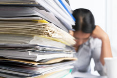 Heavy workload. Concept with pile of paper and woman on background. Selective focus Royalty Free Stock Image