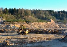 Heavy Yellow Dump Truck Unloads Soil in an Open-cast Mining Sand Pit. Heavy Yellow Dump Truck Unloads Soil in an Open-cast royalty free stock images