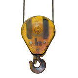 Heavy yellow rusted crane hook of an old factory isolated. On white royalty free stock images