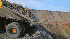 Heavy tipper truck on the quarry unloads earth