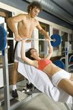 Heavyweight. Young couple, working out in gym. Man is helping woman. Woman is lying on bench and picking up dumbbell. Smiling and looking at man. Side view Stock Photography
