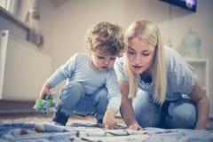 Heb binnenshuis spel met Mama Little Boy stock foto