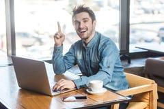 Heb idee! Het portret van creatieve positieve gebaarde jonge freelancer in jeansoverhemd zit in koffie en werkt aan laptop royalty-vrije stock foto's