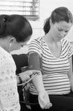 Hebamme überprüft Blutdruck der schwangeren Frau Stockbild