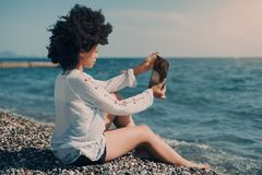 Heban dziewczyna bierze selfie podczas gdy siedzący na plaży zdjęcia royalty free