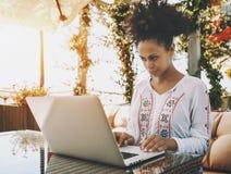 Heban dziewczyna z laptopem w ulicznej kawiarni Obraz Stock