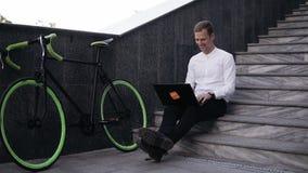 Hebbend kans overal te werken Knappe jonge aan laptop werken en mens die terwijl het zitten op moderne stad glimlachen stock videobeelden