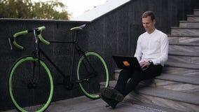 Hebbend kans overal te werken Knappe jonge aan laptop werken en mens die terwijl het zitten op moderne stad glimlachen stock footage