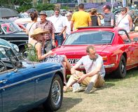 People looking at classic cars and a seated couple having a picnic at the Annual Hebden Bridge Vintage Weekend Vehicle Show royalty free stock photography