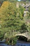 Hebden brostad i sommar med packhästbron som korsar floden calder och stenbyggnader i sommar med ljus himmel Fotografering för Bildbyråer