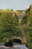 Hebden brostad i sommar med packhästbron som korsar floden calder och stenbyggnader i sommar med ljus himmel Royaltyfri Bild