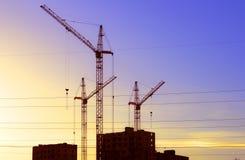 Heben Sie den Kran an, der ein neues Wohngebäude errichtet Lizenzfreies Stockfoto