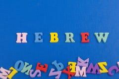 HEBRÄISCHES Wort auf dem blauen Hintergrund verfasst von den hölzernen Buchstaben des bunten ABC-Alphabetblockes, Kopienraum für  Stockfotografie