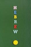 HEBRÄISCHES Wort auf dem grünen Hintergrund verfasst von den hölzernen Buchstaben des bunten ABC-Alphabetblockes, Kopienraum für  Lizenzfreie Stockbilder