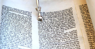 Hebrew bible scroll. Reading open bible text in book scroll torah with silver finger royalty free stock photos