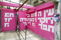 Hebrew text wall art from Tel Aviv. Tel Aviv, Israel - June 6, 2018: Mural art, white letters in magenta background with Hebrew letters found in the streets of royalty free stock photo