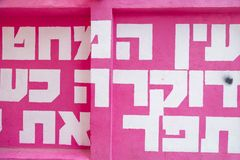 Hebrew text wall art from Tel Aviv. Tel Aviv, Israel - June 6, 2018: Mural art, white letters in magenta background with Hebrew letters found in the streets of royalty free stock images
