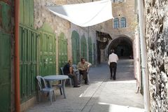 Hebron. Arab men are sitting along the street at the table bar in the old town of Hebron, arab sector, palestinian sector, where many shop are closed, Israel Royalty Free Stock Photos