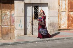 Arabic or muslim woman carrying child at Hebron streets royalty free stock images