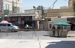 Hebron. Israeli soldiers, seen from arab sector of Hebron, stand guard at the checkpoint at the border between the israeli territory and palestinian territory in stock image