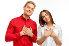 Hebt de goedaardige aantrekkelijke jongeren een vriendschappelijke uitdrukking, houdt handen op hart royalty-vrije stock afbeeldingen