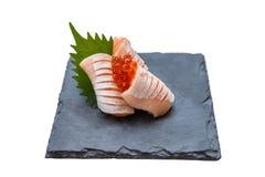 Hecho aislado Salmon Sashimi Served con Ikura Salmon Roe y rábano cortado en la placa de piedra Imagenes de archivo