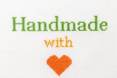 Hecho a mano con la puntada cruzada bordada frase del amor Foto de archivo libre de regalías