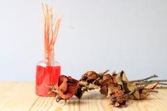 Hecho a mano del difusor de la fragancia fijado: la botella con los palillos del aroma y la rosa seca del rojo recubren con caña  fotografía de archivo libre de regalías