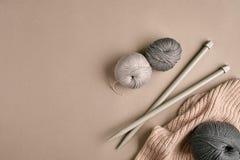 Hecho punto de un suéter y de un hilo grises del hilado para el primer que hace punto El hacer punto como afición Accesorios para Imagen de archivo libre de regalías