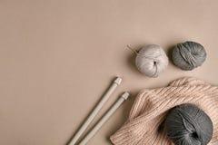 Hecho punto de un suéter y de un hilo grises del hilado para el primer que hace punto El hacer punto como afición Accesorios para Imágenes de archivo libres de regalías