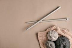 Hecho punto de un suéter y de un hilo grises del hilado para el primer que hace punto El hacer punto como afición Accesorios para Foto de archivo libre de regalías