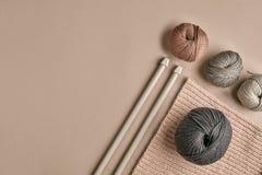 Hecho punto de un suéter y de un hilo grises del hilado para el primer que hace punto El hacer punto como afición Accesorios para Imagenes de archivo