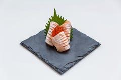Hecho Salmon Sashimi Served con Ikura Salmon Roe y rábano cortado en la placa de piedra Fotografía de archivo