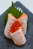 Hecho Salmon Sashimi Served con Ikura Salmon Roe y rábano cortado en la placa de piedra Imagenes de archivo
