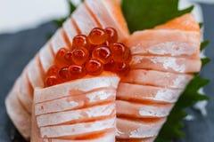 Hecho Salmon Sashimi Served con Ikura Salmon Roe y rábano cortado en la placa de piedra Imagen de archivo libre de regalías