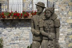 An old statue of young couple in front of balcony with red flowers. HECHO, SPAIN - SEPTEMBER 29, 2015: An old statue presents a couple of man and a women in royalty free stock photos