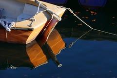 Heck eines Bootes und der Reflexion im dunkelblauen Wasser, Kopienraum Stockbilder