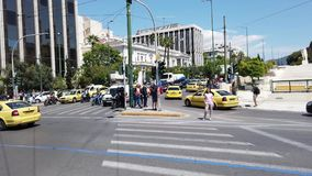 Busy traffic in central Athens CBD, Greece. Hectic and busy traffic, including many yellow taxis and motor scooters or bikes, passing through an intersection stock video