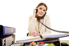 Hectic at the workplace. Young businesswoman on two phones taking notes Royalty Free Stock Photos