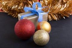 Heden en Kerstmisballen op zwarte horizontale achtergrond Stock Afbeeldingen