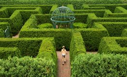 Hedge Maze A. Seen from above, a girl runs through a beautiful hedge maze with a gazebo at the center stock photo