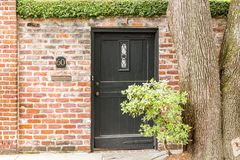 Black Portal Number 60. A hedge, tree, shrub, and a brick wall guide towards a small door label sixty Stock Image