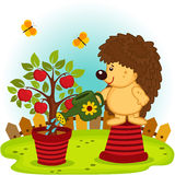 Hedgehog watering a tree with apples Royalty Free Stock Photo